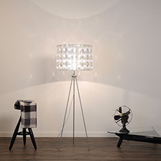 tripod floor lamp with lighthouse shade beside fan and stool