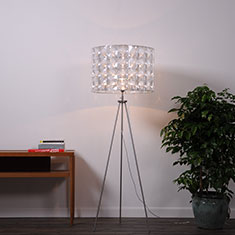 tripod floor lamp with lighthouse shade beside plant and table