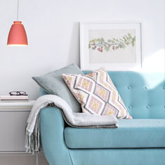 chelsea aluminium pendant light in terracotta beside a living room sofa