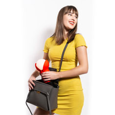 woman removing a portable fluro red bud lamp from her handbag