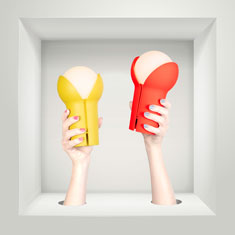 hands holding portable bud lamps in the colours lemon and fluro